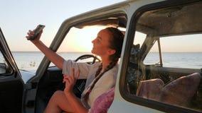 Τα βίντεο από τις διακοπές, ευτυχές θηλυκό στο αυτοκίνητο κάνουν το selfi στη συσκευή στον ήλιο, η νέα γυναίκα κάνει τις εικόνες  απόθεμα βίντεο