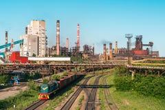 Τα βαγόνια εμπορευμάτων φορτηγών τρένων φορτίου πηγαίνουν στο σιδηρόδρομο στη βιομηχανική ζώνη με τις εγκαταστάσεις και τα εργοστ Στοκ φωτογραφία με δικαίωμα ελεύθερης χρήσης