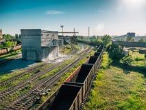 Τα βαγόνια εμπορευμάτων φορτηγών τρένων φορτίου πηγαίνουν στο σιδηρόδρομο στη βιομηχανική ζώνη με τις εγκαταστάσεις και τα εργοστ Στοκ εικόνες με δικαίωμα ελεύθερης χρήσης