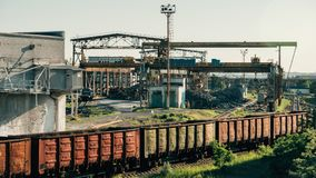 Τα βαγόνια εμπορευμάτων φορτηγών τρένων φορτίου πηγαίνουν στο σιδηρόδρομο στη βιομηχανική ζώνη με τις εγκαταστάσεις και τα εργοστ Στοκ εικόνα με δικαίωμα ελεύθερης χρήσης