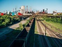 Τα βαγόνια εμπορευμάτων φορτηγών τρένων φορτίου πηγαίνουν στο σιδηρόδρομο στη βιομηχανική ζώνη με τις εγκαταστάσεις και τα εργοστ Στοκ Εικόνες