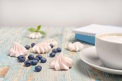 Τα βακκίνια και marshmallow βάζουν στο γραφείο κοντά σε ένα φλυτζάνι και ένα βιβλίο latte στοκ εικόνα με δικαίωμα ελεύθερης χρήσης