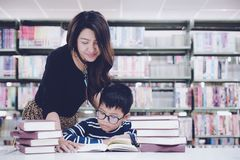 Τα βιβλία ανάγνωσης μαθητών για την εκπαίδευση και πηγαίνουν στο σχολείο με την καθοδήγηση του δασκάλου της στη βιβλιοθήκη στοκ φωτογραφίες