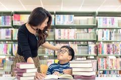 Τα βιβλία ανάγνωσης μαθητών για την εκπαίδευση και πηγαίνουν στο σχολείο με την καθοδήγηση του δασκάλου του στη βιβλιοθήκη στοκ εικόνες με δικαίωμα ελεύθερης χρήσης