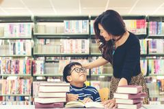 Τα βιβλία ανάγνωσης μαθητών για την εκπαίδευση και πηγαίνουν στο σχολείο με την καθοδήγηση του δασκάλου του στη βιβλιοθήκη στοκ φωτογραφίες
