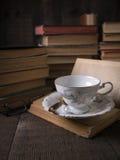 τα βιβλία κοιλαίνουν το παλαιό τσάι ανάγνωσης στοκ φωτογραφία με δικαίωμα ελεύθερης χρήσης