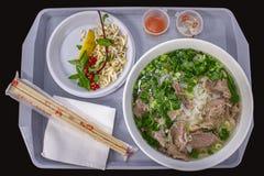 Τα βιετναμέζικα τρόφιμα οδών, σούπα του BO pho με τα πράσινα και τα νουντλς αλευριού ρυζιού, πλαστικός δίσκος εξυπηρέτησαν με ένα στοκ εικόνα με δικαίωμα ελεύθερης χρήσης