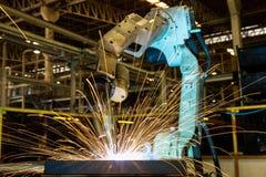 Τα βιομηχανικά ρομπότ ενώνουν στενά το αυτοκίνητο μέρος συνελεύσεων στο εργοστάσιο αυτοκινήτων Στοκ φωτογραφία με δικαίωμα ελεύθερης χρήσης