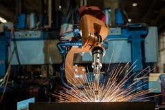 Τα βιομηχανικά ρομπότ ενώνουν στενά το μέρος συνελεύσεων στο εργοστάσιο αυτοκινήτων στοκ φωτογραφία