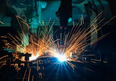 Τα βιομηχανικά ρομπότ συγκόλλησης είναι συγκόλληση μετακίνησης στη γραμμή παραγωγής Στοκ Εικόνες