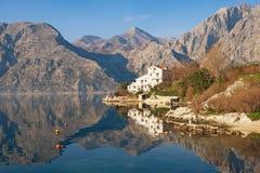 Τα βουνά και η ακτή με το άσπρο κτήριο απεικονίζονται στο νερό Μαυροβούνιο, κόλπος Kotor Στοκ εικόνα με δικαίωμα ελεύθερης χρήσης