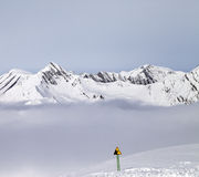 Τα βουνά στην υδρονέφωση και την προειδοποίηση τραγουδούν στην κλίση σκι Στοκ εικόνα με δικαίωμα ελεύθερης χρήσης