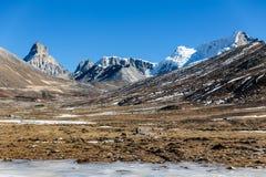 Τα βουνά witn χιονίζουν και κατωτέρω με τους τουρίστες στο έδαφος με την καφετιά χλόη, το χιόνι και την παγωμένη λίμνη το χειμώνα Στοκ φωτογραφία με δικαίωμα ελεύθερης χρήσης