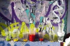 Τα βρώμικα πολύχρωμα πλαστικά γυαλιά από κάτω από τους χυμούς στέκονται στην προεξοχή του τοίχου Στοκ εικόνες με δικαίωμα ελεύθερης χρήσης