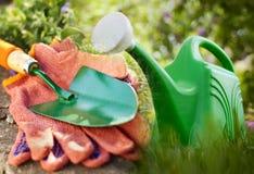 Τα γάντια κηπουρικής με ένα trowel και πότισμα μπορούν Στοκ Φωτογραφία