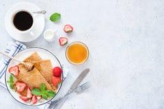 Τα γαλλικά crepes με τις φράουλες, το μέλι και το φλιτζάνι του καφέ στον πίνακα στοκ φωτογραφίες