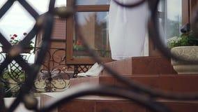 Τα γαμήλια άσπρα παπούτσια κινηματογραφήσεων σε πρώτο πλάνο είναι στα σκαλοπάτια μιας ιδιωτικής κατοικίας Ασθενής άνεμος ημέρας γ απόθεμα βίντεο
