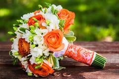 Τα γαμήλια δαχτυλίδια βρίσκονται και όμορφη ανθοδέσμη στοκ εικόνες