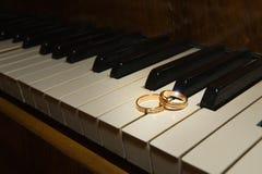 Τα γαμήλια δαχτυλίδια βρίσκονται στα γραπτά κλειδιά του πιάνου Στοκ φωτογραφίες με δικαίωμα ελεύθερης χρήσης