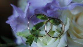 Τα γαμήλια δαχτυλίδια σε μια ανθοδέσμη των άσπρων λουλουδιών κλείνουν επάνω Γαμήλια δαχτυλίδια και ανθοδέσμη του σκούρο μπλε λουλ Στοκ φωτογραφία με δικαίωμα ελεύθερης χρήσης