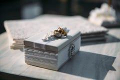 Τα γαμήλια χρυσά δαχτυλίδια σε ένα διακοσμητικό άσπρο κιβώτιο, βρίσκονται στον πίνακα Έννοια κοσμήματος Στοκ εικόνες με δικαίωμα ελεύθερης χρήσης
