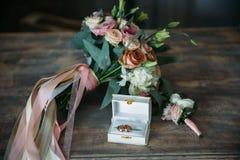 Τα γαμήλια χρυσά δαχτυλίδια σε ένα διακοσμητικό μαξιλάρι με τη νύφη ανθίζουν και καλλωπίζουν τη μπουτονιέρα Έννοια κοσμήματος Στοκ Εικόνες