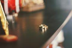Τα γαμήλια δαχτυλίδια βρίσκονται και λαμπιρίζουν σε έναν πίνακα επιδέσμου Στοκ Εικόνες