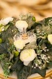 Τα γαμήλια δαχτυλίδια βρίσκονται σε ένα πιάτο στο γραφείο ληξιαρχείων Στοκ Εικόνες