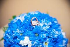 Τα γαμήλια δαχτυλίδια βρίσκονται σε μια ανθοδέσμη Στοκ Εικόνες