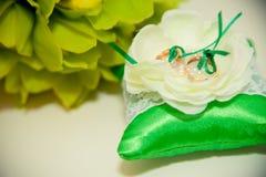 Τα γαμήλια δαχτυλίδια βρίσκονται στο μαξιλάρι για τα δαχτυλίδια Στοκ Εικόνες