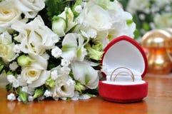 Τα γαμήλια δαχτυλίδια και άσπρος αυξήθηκαν ανθοδέσμη Στοκ Εικόνες