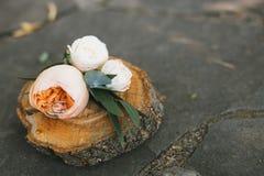 Τα γαμήλια δαχτυλίδια μέσα headband λουλουδιών αυξήθηκαν σε ένα ξύλινο κολόβωμα Στοκ εικόνα με δικαίωμα ελεύθερης χρήσης