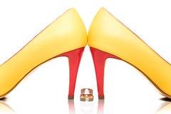 Τα γαμήλια δαχτυλίδια με την ημερομηνία γεγονότος χάραξαν σε τους εκτός από τα ασυνήθιστα σύγχρονα πολύχρωμα νυφικά παπούτσια στο Στοκ φωτογραφία με δικαίωμα ελεύθερης χρήσης