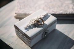 Τα γαμήλια χρυσά δαχτυλίδια σε ένα διακοσμητικό άσπρο κιβώτιο, βρίσκονται στον πίνακα Έννοια κοσμήματος Στοκ Φωτογραφία