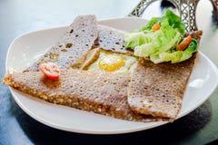 Τα γαλλικά crepe με τη φέτα κοτόπουλου, τυρί, το αυγό στο άσπρο πιάτο τρώει με την πράσινη ντομάτα σαλάτας και κερασιών Στοκ Εικόνα
