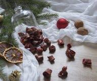 Τα γλασαρισμένα φρούτα ζυμαρικών μούρων φραουλών ξηρών καρπών σε έναν πίνακα κάτω από ένα χριστουγεννιάτικο δέντρο γυαλιού ΚΑΠ χτ Στοκ Φωτογραφίες