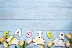 Τα γλυκά για γιορτάζουν Πάσχα Μελόψωμο στη μορφή του λαγουδάκι και της επιστολής Πάσχα, τουλίπες Πάσχας Στοκ Φωτογραφίες
