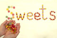Τα γλυκά μιας λέξης ευθυγράμμισαν με τις καραμέλες σε ένα ελαφρύ υπόβαθρο στοκ εικόνες