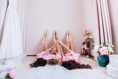 Τα γοητευτικά κορίτσια που βρίσκονται επάνω με τα όπλα αύξησαν τα διασχισμένα πόδια, εορτασμός ενός γεγονότος διακοπών γενεθλίων στοκ φωτογραφία
