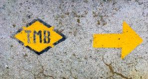 Τα γράμματα TMB που σημαίνουν το πεζοπορώ γύρου du Mont Blanc και μια κατεύθυνση arrrow χρωμάτισαν σε έναν βράχο Στοκ φωτογραφίες με δικαίωμα ελεύθερης χρήσης