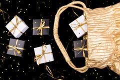 Τα γραπτά κιβώτια δώρων με τη χρυσή κορδέλλα λαϊκή έξω από τη χρυσή τσάντα λάμπουν επάνω υπόβαθρο Επίπεδος βάλτε Στοκ Εικόνες