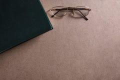 Τα γυαλιά βρίσκονται κοντά στην πράσινη βίβλο στο ξύλινο υπόβαθρο Η έννοια της ανάγνωσης και της εκπαίδευσης E στοκ φωτογραφία