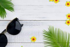 Τα γυαλιά ηλίου διακοσμούν με τα φύλλα φτερών και τα κίτρινα λουλούδια εγγράφου Στοκ φωτογραφίες με δικαίωμα ελεύθερης χρήσης