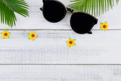 Τα γυαλιά ηλίου διακοσμούν με τα φύλλα φτερών και τα κίτρινα λουλούδια εγγράφου Στοκ Εικόνες