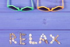 Τα γυαλιά ηλίου και η λέξη χαλαρώνουν φιαγμένος από θαλασσινά κοχύλια, θερινός χρόνος, διάστημα αντιγράφων για το κείμενο στους π Στοκ Φωτογραφία