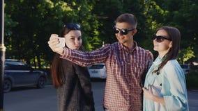 Τα γυαλιά ηλίου φίλων κάνουν selfie Άνδρας και δύο γυναίκες φιλμ μικρού μήκους
