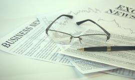 Τα γυαλιά και η μάνδρα ανάγνωσης είναι στα ειδησεογραφικά μέσα στοκ φωτογραφίες