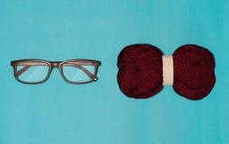 Τα γυαλιά και το τόξο βρίσκονται κοντά σε ένα μπλε υπόβαθρο στοκ εικόνες με δικαίωμα ελεύθερης χρήσης