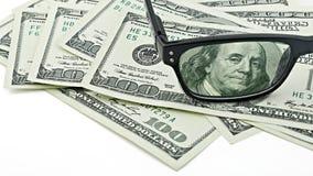 Τα γυαλιά κινηματογραφήσεων σε πρώτο πλάνο στις ΗΠΑ 100 εκατό δολάρια τιμολογούν ή τραπεζογραμμάτιο που απομονώνεται στο άσπρο υπ Στοκ Εικόνες