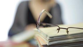 Τα γυαλιά σε έναν σωρό των βιβλίων άσκησης, γυναίκα λειτουργούν χωρίς γυαλιά μετά από τη διόρθωση οράματος απόθεμα βίντεο